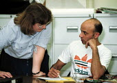 Adult education Basic Skills course lecturer helping students to learning to read and write. Organised by CATU trades union Stoke on Trent - John Harris - 02-02-2000