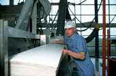 Young worker positioning card on a machine in a highly automated production line at a cardboard manufacturing and printworks. - John Harris - 23-03-2000
