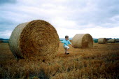Toddler of 3 yrs playing in field of spiky stubble and hay bales. - John Harris - 03-09-2002