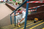 Painter painting yellow warning lines onto steps to help prevent accidents at the entrance to a hospital. - John Harris - 18-08-2002
