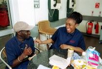 Post Office workers enjoying a joke during lunch break, Royal Mail Centre Birmingham - John Harris - 2000s,2002,BAME,BAMEs,Birmingham,black,BME,bmes,break,canteen,CANTEENS,diversity,employee,employees,Employment,enjoying,ENJOYMENT,ethnic,ethnicity,FEMALE,funny,humor,humorous,HUMOUR,job,jobs,joke,joke