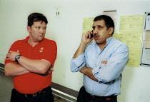 Trades Union representative and shop steward. Talking on the mobile phone, Royal Mail Centre Birmingham. - John Harris - 19-08-2002