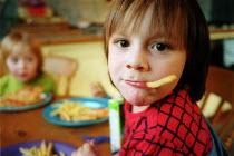 Boy eating pizza and chips. - John Harris - 2000s,2003,a,at,BOY,boys,branding,BREAK,CARE,carer,carers,cheeky,child,Child Care,childcare,CHILDHOOD,CHILDMINDING,children,chip,chips,diet,diets,DINNER,dinners,DINNERTIME,early years,eat,eating,emili