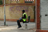 Worker waiting for a lift, sitting on a hairdressers chair on the street, Hackney London - John Harris - 31-07-2003