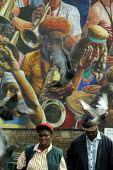 People walking down the street, with the Dalston Peace Mural behind, Hackney London - John Harris - 31-07-2003
