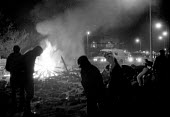 Pickets picking up stones and rocks to throw at riot police vans charging their burning barricade in the early hours of the morning. Mass picket after police managed to get a scab into the pit. Pit La... - John Harris - 17-10-1984