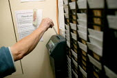 Worker clocking in a the start of his shift. - John Harris - 11-09-2003