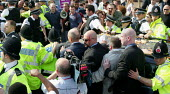 Anti fascist protesters struggle with Police and BNP bodyguards as they try to block the car of Jean-Marie Le Pen of the French National Front and Nick Griffin BNP leader. Manchester. - John Harris - 2000s,2004,activist,activists,adult,adults,Anti Fascist,bigotry,BNP,British National Party,CAMPAIGN,campaigner,campaigners,CAMPAIGNING,CAMPAIGNS,CLJ,DEMONSTRATING,demonstration,DEMONSTRATIONS,DISCRIMI