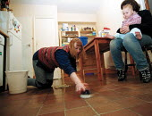 Cleaner scrubbing kitchen floor and mother caring for baby - John Harris
