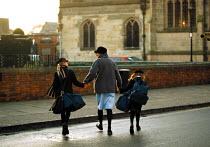 Nanny taking daughters to private preparatory school, crossing the road, Stratford on Avon - John Harris - 2000,2000s,AFFLUENCE,AFFLUENT,Bag,Bags,Bourgeoisie,CARE,carer,carers,child,Child Care,childcare,CHILDHOOD,CHILDMINDING,children,cross,crosses,crossing,early years,EDU education,education,elite,elitism