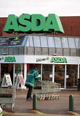 Worker moving shopping trollies ASDA supermarket - John Harris - 2000,2000s,bought,buy,buyer,buyers,buying,cart,commodities,commodity,consumer,consumers,customer,customers,EARNINGS,EBF economy business,employee,employees,Employment,goods,Income,inequality,job,jobs,
