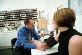 Patient consulting a medical herbalist, who is measuring her blood pressure. - John Harris - 20-02-2000