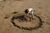 Little boy on the beach making a sand castle. Weston Super Mare, Somerset. - John Harris - 2000s,2005,beach,BEACHES,boy,boys,child,CHILDHOOD,children,circle,COAST,coastal,coasts,day out,emilio,holiday,holiday maker,holiday makers,holidaymaker,holidaymakers,holidays,juvenile,juveniles,kid,ki