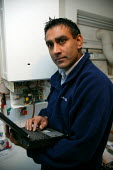 British gas heating service engineer running a diagnostic check on a domestic boiler using a laptop computer with a a newly developed GPS based mobile telephone and handheld computer and trialling opt... - John Harris - 06-12-2005