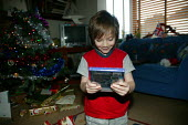 Little boy opening his presents on Christmas day morning. - John Harris - 25-12-2005