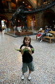 Small boy visiting The Natural History Museum, London. Standing infront of The Diplodocus skeleton in the main hall, clutching a toy Triceratops. - John Harris - 29-08-2005