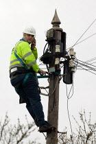 BT engineer working at a switching box up a telegraph pole. - John Harris - 18-01-2006