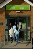 Young women going into a Jobcentre Plus. - John Harris - 2000s,2006,a,adolescence,adolescent,adolescents,agency,benefit,benefits,BENIFIT,BENIFITS,centre,centres,claim,claimant,claimants,claiming,dole,employment,FEMALE,interacting,interaction,job,job center,