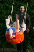 Father pushing daughter on the swings, playing on a summer evening. Warwickshire - John Harris - 02-06-2006