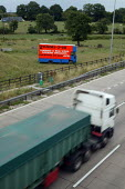 Traffic passing an illegal advertisement in a field next to the M42. These adverts distract drivers and are against safety and council planning regulations. - John Harris - 31-07-2006