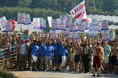 """Hundreds of young Polish migrant workers waving a Solidarnosc flag protesting at their working conditions in a """"Stop exploitation picket"""" at S and A Produce, Strawberry farm which supplies a third of... - John Harris - &,2000s,2006,A,ACTIVIST,activists,agricultural,agriculture,bme minority ethnic,campaign,campaigner,campaigners,CAMPAIGNING,CAMPAIGNS,DEMONSTRATING,DEMONSTRATION,DEMONSTRATIONS,Diaspora,DISPUTE,DISPUTE"""