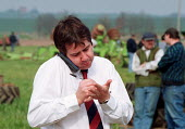 Dealer writing notes on his hand whilst making a call on his mobile phone. Farmers buying farm machinery and tools at an auction of goods of a farmer who has gone out of business. Warwickshire. 22,000... - John Harris - 2000,2000s,AGRICULTURAL,agriculture,auction,auctioneer,auctioneers,AUCTIONS,BUY,buyer,buyers,buying,call,capitalism,capitalist,CELLULAR,commodities,commodity,communicating,communication,conversation,c