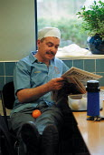 Worker reading a newspaper during his lunch break in a printing works canteen. - John Harris - 23-03-2000