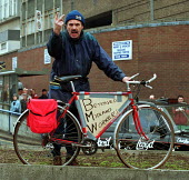 """Angry worker on his bike with """"betrayed Midland worker"""" placard. Demonsration against the break up of Rover by BMW, and loss of jobs at Longbridge, Birmingham attended by 50,000. - John Harris - 01-04-2000"""