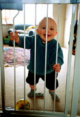 Baby boy at home in front room, 11 months of age with safety gate, football and a smile. - John Harris - 20-04-2000