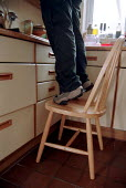 Safety in the home, women balancing on a chair in kitchen to reach shelf. - John Harris - 2000,2000s,accident,accidental,accidents,dia accident accidents,ergonomic,ergonomics,FEMALE,hazard,hazardous,hazards,health,home,in,kitchen,KITCHENS,people,person,persons,risk,risks,safety,the,unsafe,