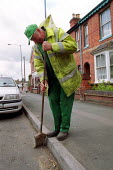 Local authority street cleaner sweeping the gutter. - John Harris - 18-05-2000