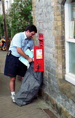 Postal worker collecting post from rural village postbox outside a post office. - John Harris - 2000,2000s,collecting,communities,community,EBF economy business,employee,employees,Employment,europeregi,job,jobs,LAB LBR work,LBR,Letter box,Letter boxes,letter letters,Letterbox,Letterboxes,MAIL,ma