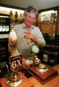 Landlord pouring a pint of bitter in a pub. - John Harris - 2000,2000s,alcohol,bar,BAR PERSON,Bar staff,bar tending,barman,BARS,Bartender,bartenders,bartending,beer,drink,Drinking,EARNINGS,EBF economy business,employee,employees,Employment,EQUALITY,Income,INCO