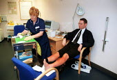 Nurse treating patients sun burn symptoms at NHS walk-in centre in Boots Birmingham, which offers assessment by an experienced NHS nurse who can give healthcare advice, information and treatment. No a... - John Harris - 16-06-2000
