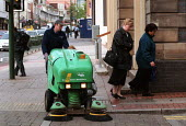 Street cleaner sweeping the pavement, as women go to work. Birmingham - John Harris - 18-05-2000