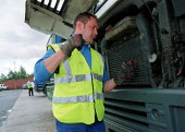 Driver checking oil level on a HGV vehicle at a chilled food products distribution centre, Express Chilled Distribution. - John Harris - ,2000,2000s,checking,distribution,Driver,Drivers,DRIVING,EBF economy business,engine,ENGINES,food,FOODS,HAULAGE,HAULIER,HAULIERS,HGV,hgvs,levels,LGV,LGVs,loading bays,Lorries,lorry,maintaining,Mainten