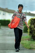 Paperboy on his delivery round with his bag of newspapers. - John Harris - 16-08-2000