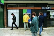Customers queue to use a cash machine at a high Street branch of Lloyds TSB bank. - John Harris - 18-09-2000