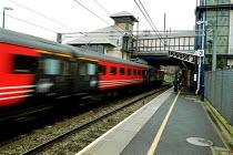 Passenger train speeding through a local railway station on the electrified east coast line. - John Harris - 07-10-2000