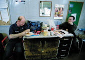Workers take a lunch break in control room, eating and reading trade press. - John Harris - 16-01-2001