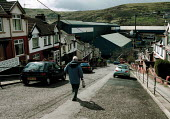 Retired steelworker walking down street of houses above Corus Ebbw Vale steelworks, South Wales valleys. - John Harris - 2000s,2001,age,ageing population,capitalism,capitalist,EBF,EBF economy,Economic,Economy,elderly,FACTORIES,factory,house,houses,housing,Industries,industry,job,jobs,LAB LBR work,maker,makers,making,met