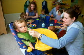 Nursery assistant feeding a toddler lunch at a day time nursery. - John Harris - 10-04-2001