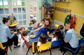 Nursery assistants feeding toddlers lunch at a day time nursery. - John Harris - 10-04-2001