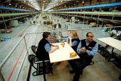 Workers take a break at Post Office Parcel Force Royal Mail Coventry Hub distribution centre. - John Harris - ,2000s,2001,asian,automated,AUTOMATIC,automation,BAME,BAMEs,black,BME,bmes,break,communicating,communication,conversation,cultural,DELIVERING,delivery,dialogue,distribution,diversity,drink,drinks,EBF
