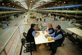 Workers take a break at Post Office Parcel Force Royal Mail Coventry Hub distribution centre. - John Harris - 2000s,2001,asian,automated,AUTOMATIC,automation,BAME,BAMEs,black,BME,bmes,break,communicating,communication,conversation,cultural,DELIVERING,delivery,dialogue,distribution,diversity,drink,drinks,EBF e