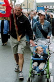 Robin and Nerys Williams with their 10 month old baby son the day Robin lost his job. Steelworkers marching out of Corus Steelworks Bryngwyn South Wales with dignity on the day that it closed. - John Harris - 2000s,2001,activist,activists,adult,adults,and,Anxiety,Anxious,ANXIOUSNESS,APPREHENSIVE,babies,baby,banner,banners,CAMPAIGN,campaigner,campaigners,CAMPAIGNING,CAMPAIGNS,Child,CHILDHOOD,children,CLOSED