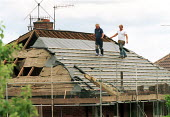Roofers balancing on rafters whilst replacing roofing tiles on housing. - John Harris - 2000s,2001,association,ASSOCIATIONS,building,BUILDINGS,construction,Construction Industry,EBF economy,health,housing,job,jobs,LAB LBR work,people,project,rafters,replacing,roof,roofer,roofs,rooftop,ro