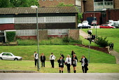 Pupils walking home from Baverstock secondary School Birmingham through housing estate. - John Harris - 2000s,2001,adolescence,adolescent,adolescents,Birmingham,Boarded Up,boy,boys,child,CHILDHOOD,children,cities,city,Comprehensive School,council estate,council services,council estate,council services,E