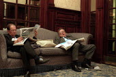 Businessman reading newspapers and sleeping on a settee in a Hotel lobby. - John Harris - 20-09-2000