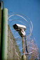 Security camera and razor wire along the fence. Campsfield Detention Centre. - John Harris - 2000s,2001,Asylum Seeker,Asylum Seekers,Asylum Seeker,Asylum Seekers,camera,cameras,cctv,center,centre,CLJ,crime prevention,deportation,deportations,deporting,detained,detainee,detainees,detention,Det